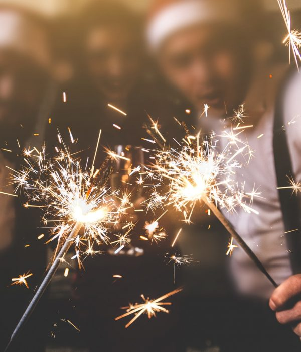 sparklers in the foreground. Beautiful young people at a corporate party. New Year celebration. Club party with friends.